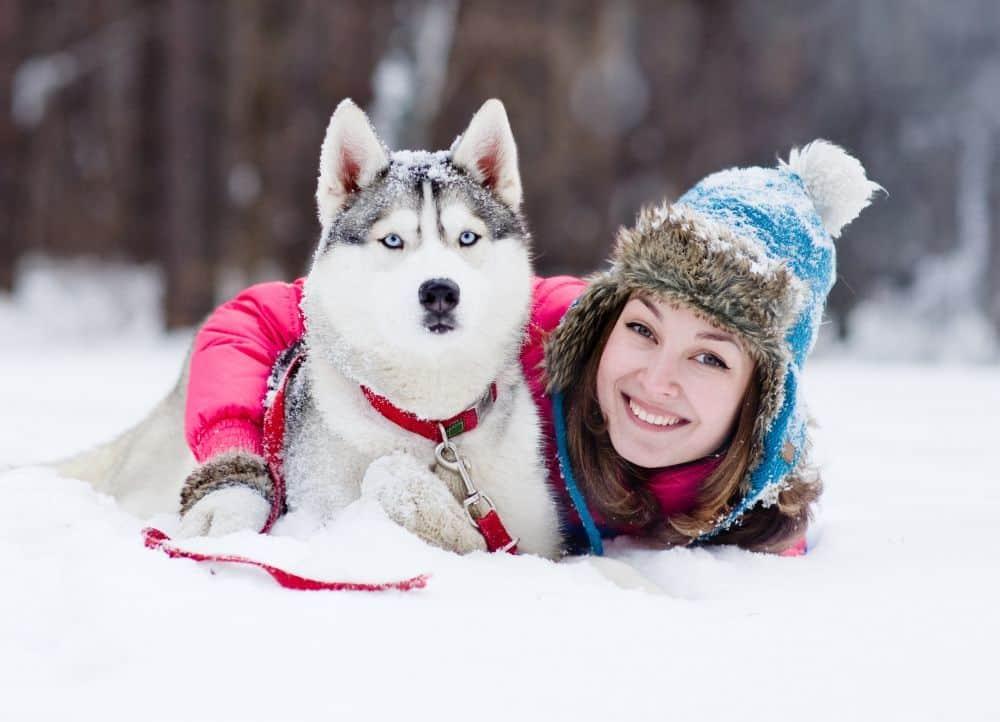 Husky mit junge Frau im Schnee